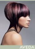Netradiční účes z polodlouhých vlasů, silně prostříhaných od urovně brady, fialové barvy se světlefialovým melírem