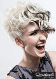 Krátký blond účes s divokými vlnkami a černými proužky