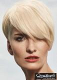 Krátký blond střih s patkou spadenou přes oko