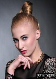 Účes z blond vlasů vyčesaný do nevšedního drdolu