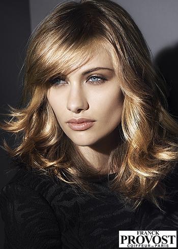 Zvlněný účes z hnědých vlasů s blond melírem a ofinou