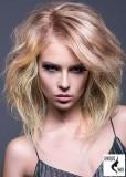 Objemný blond zvlněný účes s pěšinou na stranu