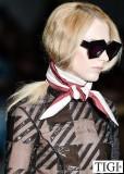 Dlouhé blond vlasy svázané ke krku šátkem