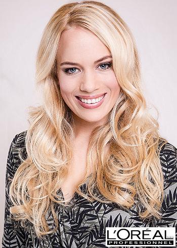Dlouhé zvlněné blond vlasy s pěšinou na bok