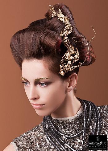 Nevšední společenský účes vyčesaný nahoru z krepovaných vlasů se zlatou ozdobou