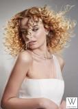 Dlouhý kudrnatý blond účes s pěšinou uprostřed