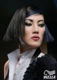 Krátký, extravagantně vystylovaný účes hranatého vzhledu s modrým melírem