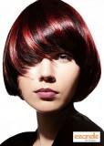 Krátký asymetricky střižený účes se šikmou ofinou, černé barvy s červenými akcenty