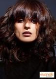 Dlouhý účes z kudrnatých postupně sestříhaných vlasů s rovnou ofinkou do čela hnědočervené barvy