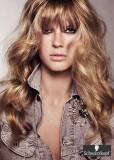 Romantický účes z vlnitých dlouhých vlasů hnědé barvy s blond melírem a s rovnou ofinou do čela