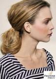 Účes z dlouhých rovných vlasů hnědé barvy s blond melírem,  na krku vyčesaný do natupírovaného culíku