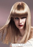 Účes z dlouhých rovně střižených hladkých blond vlasů s hustou rovnou ofinou do čela