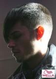 Pánský velmi krtký účes s dlouhou ofinou stylizovanou do špičky do čela, nazelenalé barvy