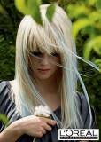 Geometricky střižený účes z dlouhých rovných blond vlasů s modrým melírem a ofinou do čela