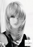 Účes z dlouhých rovných vlasů blond barvy, podél obličeje výrazně postupně sestříhaný, s rovnou ofinou
