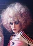 Extravagantní účes z natupírovaných a zvlněných polodlouhých blond vlasů s růžovým melírem