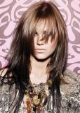 Dlouhý účes z rovných postupně sestříhaných vlasů, hnědé barvy postupně měnící tony od kořínků ke konečkům