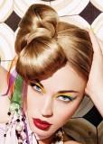 Extravagantní účes vyčesaný z dlouhých rovných blond vlasů, do mašle