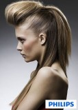 Účes z dlouhých rovných vlasů hnědé barvy s blond melírem, z horné poloviny vyčesaný extravagantní culík
