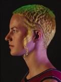 Extravagantní účes z krátkých rovných vlasů žluté barvy se zeleným melírem, po stranách sestříhaný do vln, s volně spuštěným pra