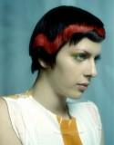 Krátký extravagantní účes z rovných vlasů černé barvy, sestříhaný, s červeným pruhem vedeným do vlny