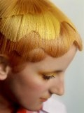 Extravagantní účes z rovných krátkých vlasů sestříhaných do vln, s různými tony oranžové barvy