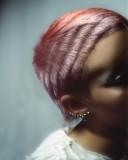 Extravagantní schodkovitě sestříhaný účes z rovných krátkých vlasů blond barvy s melírem pastelových barev