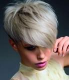 Moderní sestříhaný účes z krátkých rovných vlasů bílé barvy s dlouhou ofinou na straně přez oko