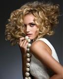 Extravagantní polodlouhé mikádo ze silně zvlněných vlasů blond barvy s pěšinou na straně