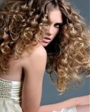Účes z dlouhých velmi hustých zvlněných vlasů hnědé barvy se světlým melírem a s pěšinkou uprostřed