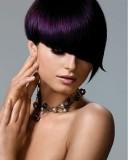 Extravagantní účes z krátkých rovných vlasů tmavofialové barvy, s ofinou šikmo střiženou do očí