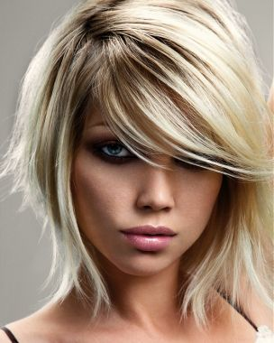 Polodlouhý sestříhaný účes z rovných vlasů blond barvy s jemným tmavohnědým melírem, s ofinkou na straně