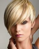 Krátký asymetricky třížený účes z rovných vlasů blond barvy s melírem ton v tonu, s přední partií přez oko