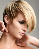 Extravagantní účes z krátkých sestříhaných vlasů blond barvy s melírem, s přední částí na temeni natužené dopředu