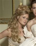 Romantický účes do společnosti, z dlouhých zvlněných vlasů blond barvy, částečně vyčesaný