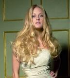 Účes z velmi dlouhých zvlněných vlasů blond barvy s pěšinkou uprostřed