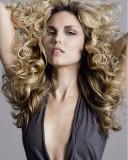Sexy účes z dlouhých vlasů z velkých vln, blond barvy s jemným světlehnědým melírem