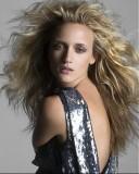 Rozfoukaný účes z dlouhých zvlněných vlasů světlhnedé barvy s blond melírem