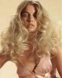 Účes z velmi hustých dlouhých zvlněných vlasů blond barvy s pěšinkou uprostřed