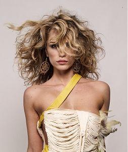 Rozevlátý účes z dlouhých vlnitých vlasů světlehnědé barvy s blond melírem
