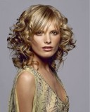 Něžný účes z polodlouhých zvlněných vlasů blond barvy s rovnou ofinou na straně