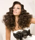 Sexy účes z dlouhých zvlněných vlasů tmavohnědé barvy, s pěšinkou na straně