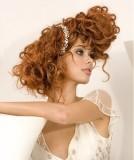 Extravagantně vyčesaný svatební účes z vlnitých vlasů měděné barvy
