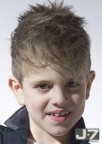 Dětský účes z krátkých rovných vlásků světlehnědé barvy, stylizovaný do rozcuchu