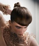Netradiční vyčesaný společenský účes z dlouhých rovných vlasů hnědé barvy, s drdolem vzadu na temeni