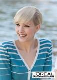 Krátký uhlazený účes z rovných vlasů blond barvy, s dlouhou ofinou do čela