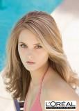 Romantický účes z dlouhých mírně zvlněných vlasů světlehnědé barvy s blond melírem a pěšinou na straně