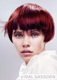Nepravidelně sestříhané mikádo z krátkých vlasů červené barvy s melírem a hustou ofinou do čela