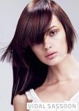 Asymetricky střižený účes z dlouhých rovných vlasů hnědé barvy se světlým melírem a ofinou do čela