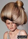 Extravagantní účes z dlouhých rovných vlasů vyčesaných nahoru, hnědé barvy s blond melírem
